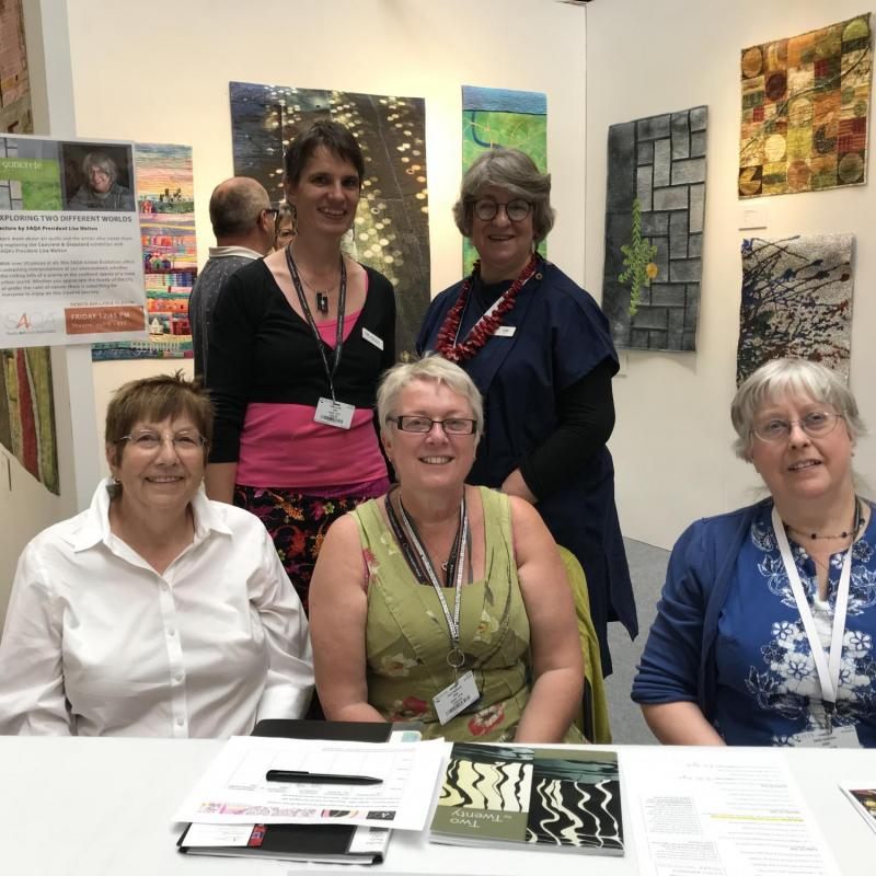Festival of Quilts 2018 – SAQA members stewarding the SAQA Global exhibit on display - photo credit: Thilo Schueller